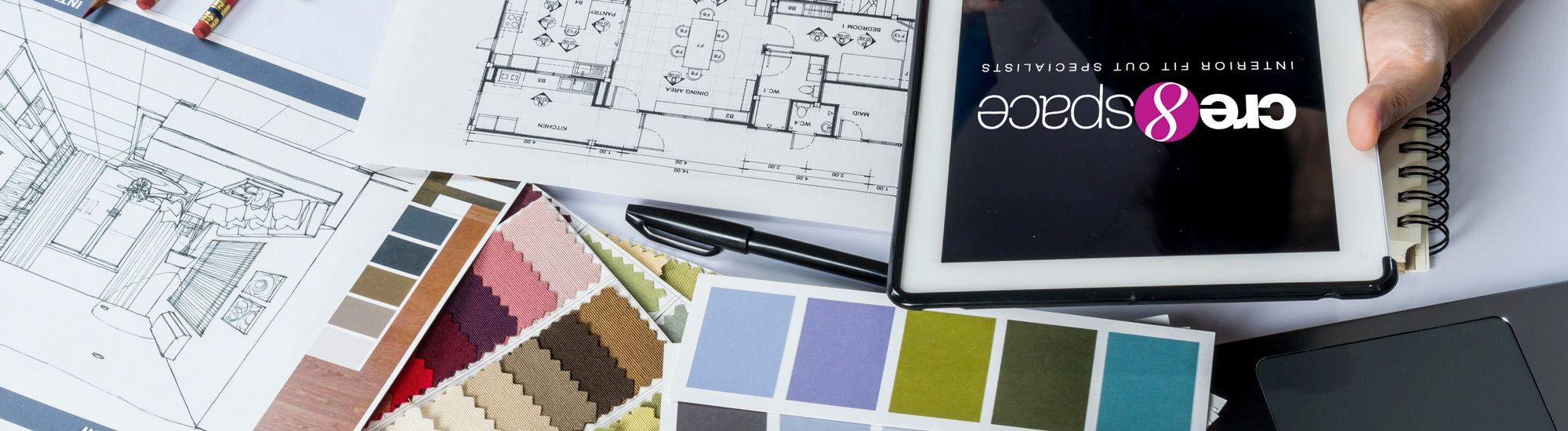 Office designer using tablet and blueprints for interior design